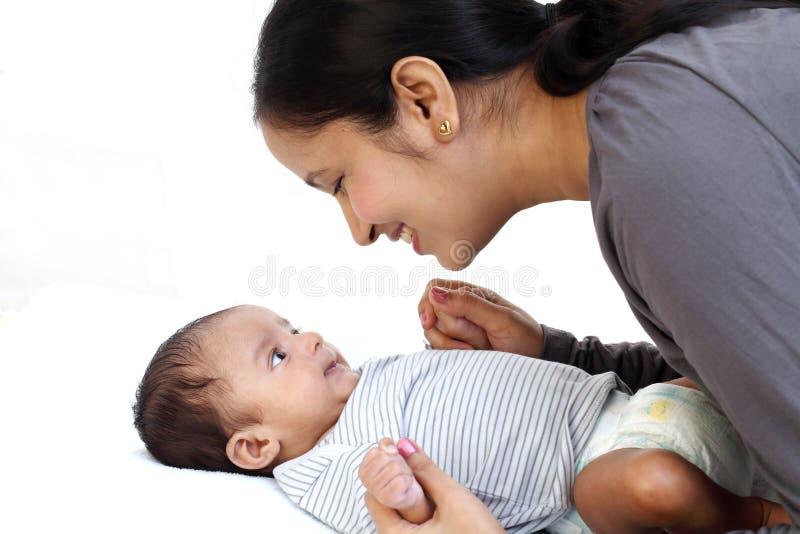 Mère gaie jouant avec nouveau-né images stock