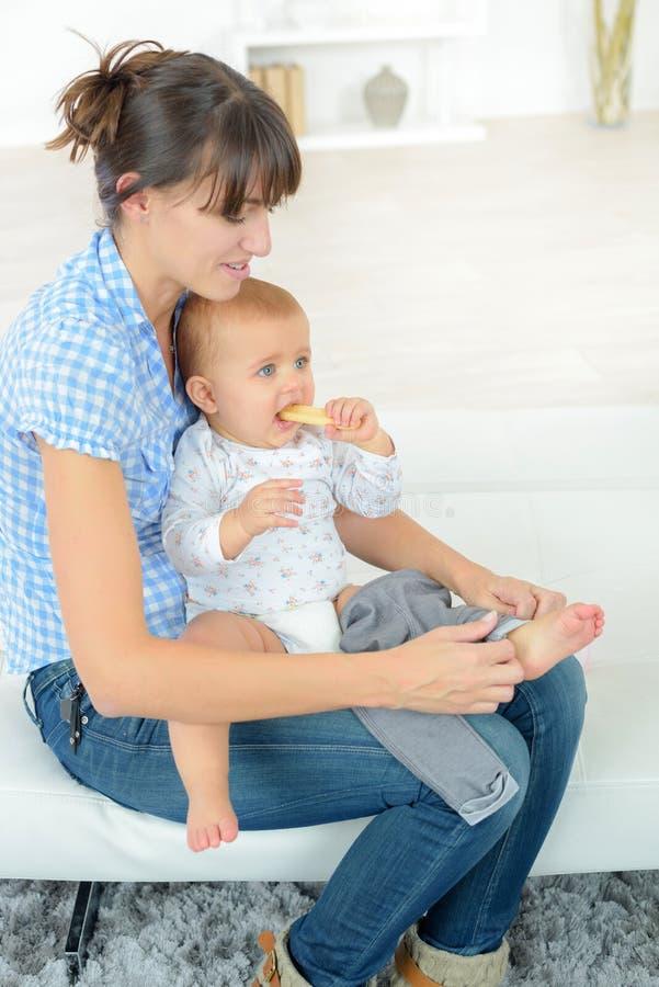 Mère habillant le bébé sur le divan photo libre de droits