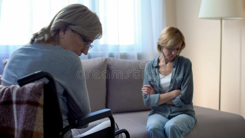 Mère handicapée pluse âgé parlant avec la fille bouleversée, problèmes de famille, querelle images libres de droits
