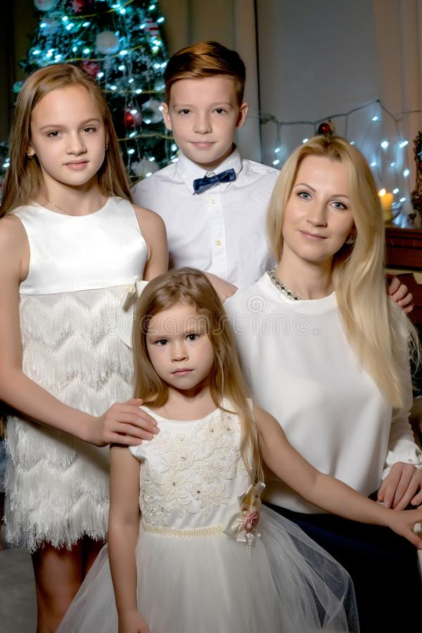 Mère heureuse avec des enfants près d'un piano à queue blanc photos stock