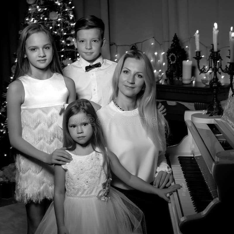 Mère heureuse avec des enfants près d'un piano à queue blanc image stock