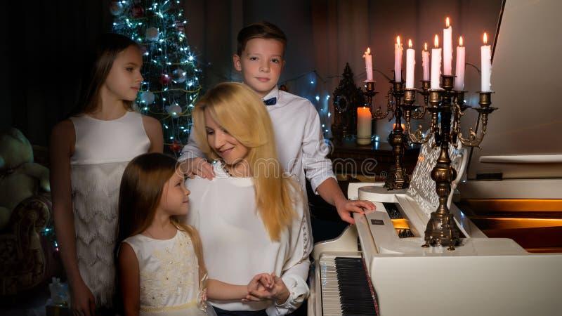 Mère heureuse avec des enfants près d'un piano à queue blanc photo stock