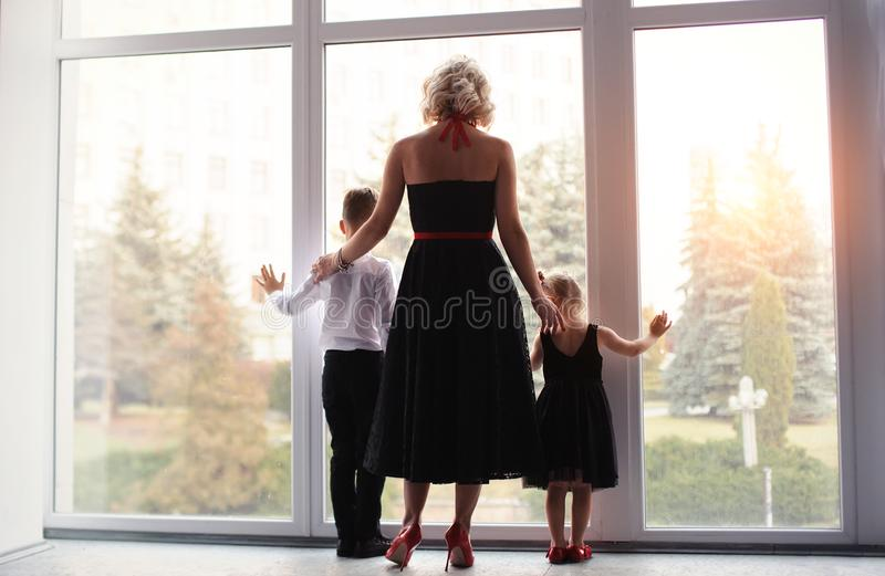 mère heureuse avec enfants près de la fenêtre image libre de droits