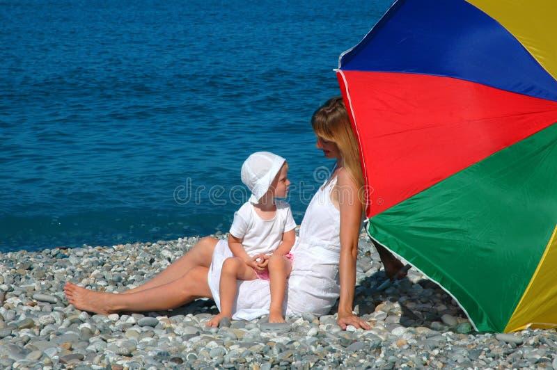 Mère heureuse avec l'enfant sous le parapluie sur la plage photographie stock libre de droits