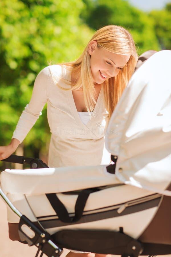 Mère heureuse avec la poussette en parc photo stock
