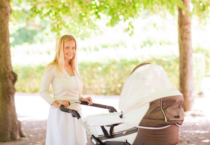 Mère heureuse avec la poussette en parc image stock