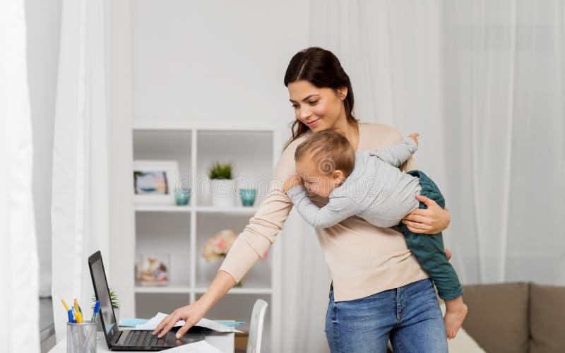 Mère heureuse avec le bébé et ordinateur portable fonctionnant à la maison photos libres de droits