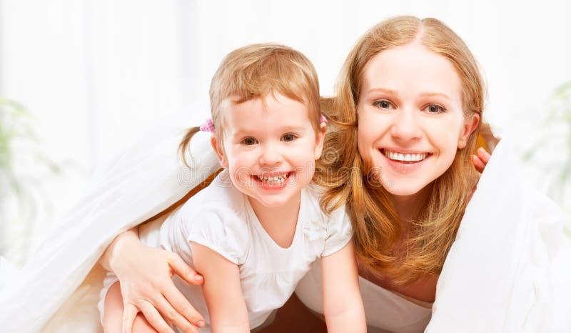 Mère heureuse de famille et fille de bébé d'enfant jouant dans le lit photographie stock libre de droits