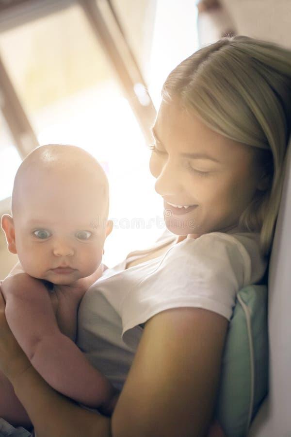 Mère heureuse de sourire avec le petit bébé garçon à la maison photo stock