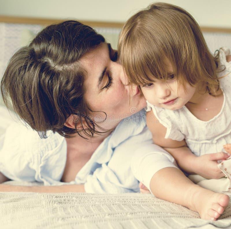 Mère heureuse embrassant la fille dans le lit photographie stock