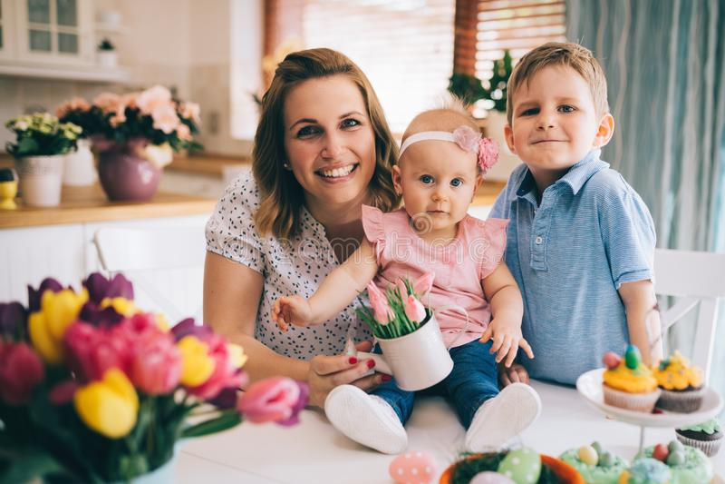 Mère heureuse et affectueuse et ses enfants préparant la décoration à la maison images stock