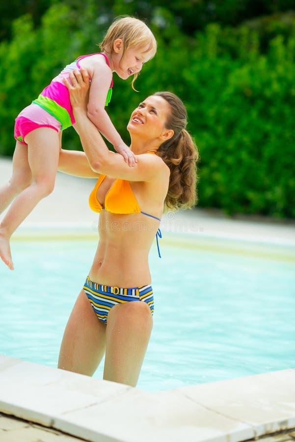 Mère heureuse et bébé jouant dans la piscine photographie stock