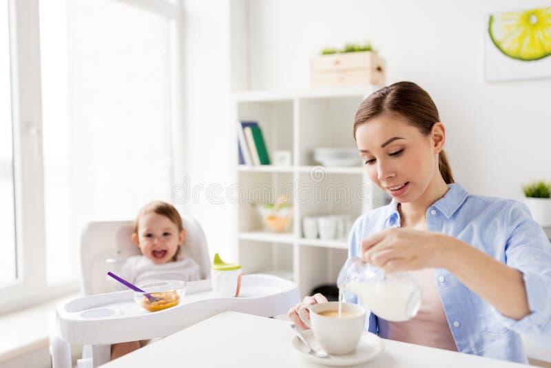 Mère heureuse et bébé prenant le petit déjeuner à la maison images stock