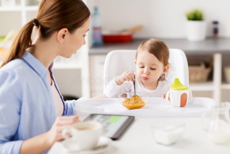 Mère heureuse et bébé prenant le petit déjeuner à la maison photos libres de droits