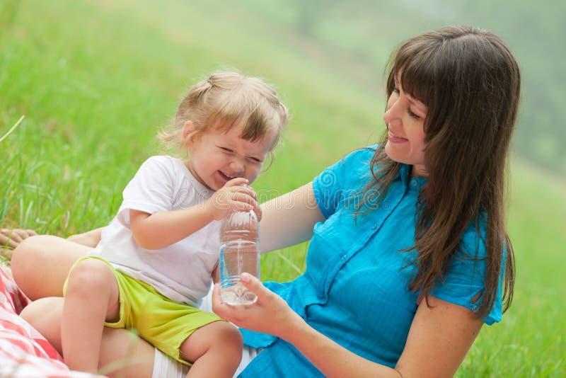 Mère heureuse et descendant buvant l'eau claire image stock