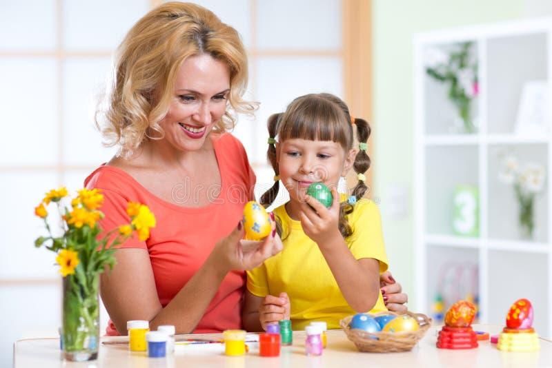 Mère heureuse et enfant peignant des oeufs de pâques images stock