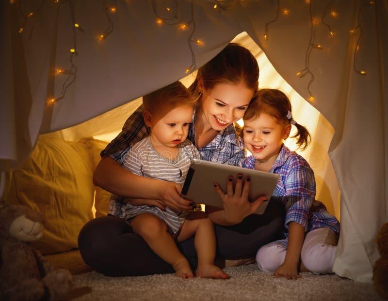 Mère heureuse et enfants de famille jouant dans le PC de comprimé photo stock