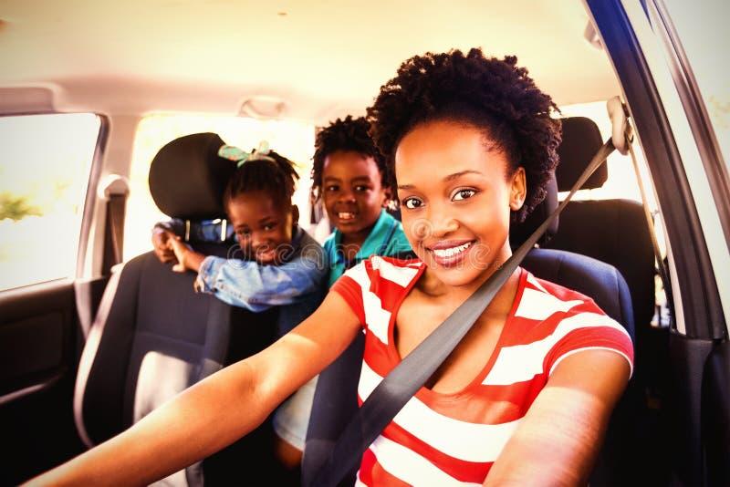 Mère heureuse et enfants s'asseyant dans la voiture images stock