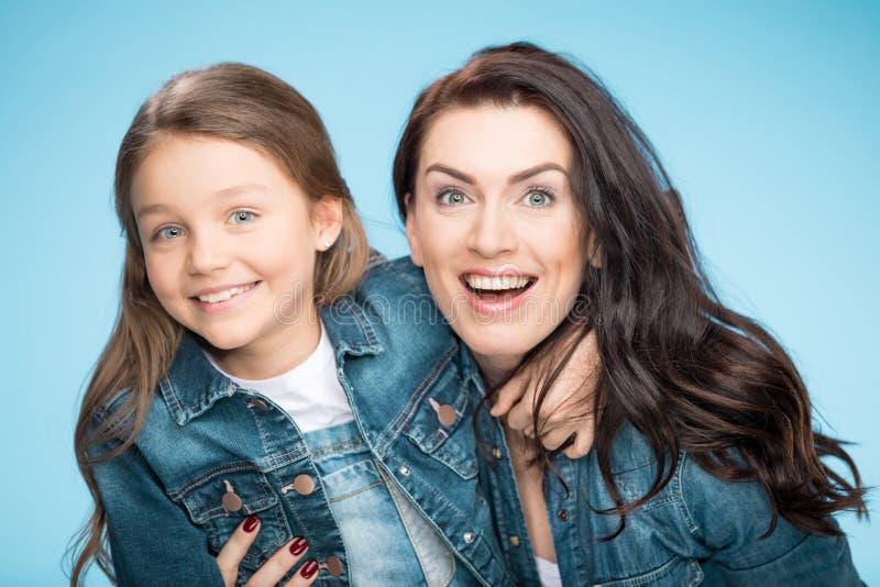 Mère heureuse et fille étreignant dans le studio sur le bleu photos stock