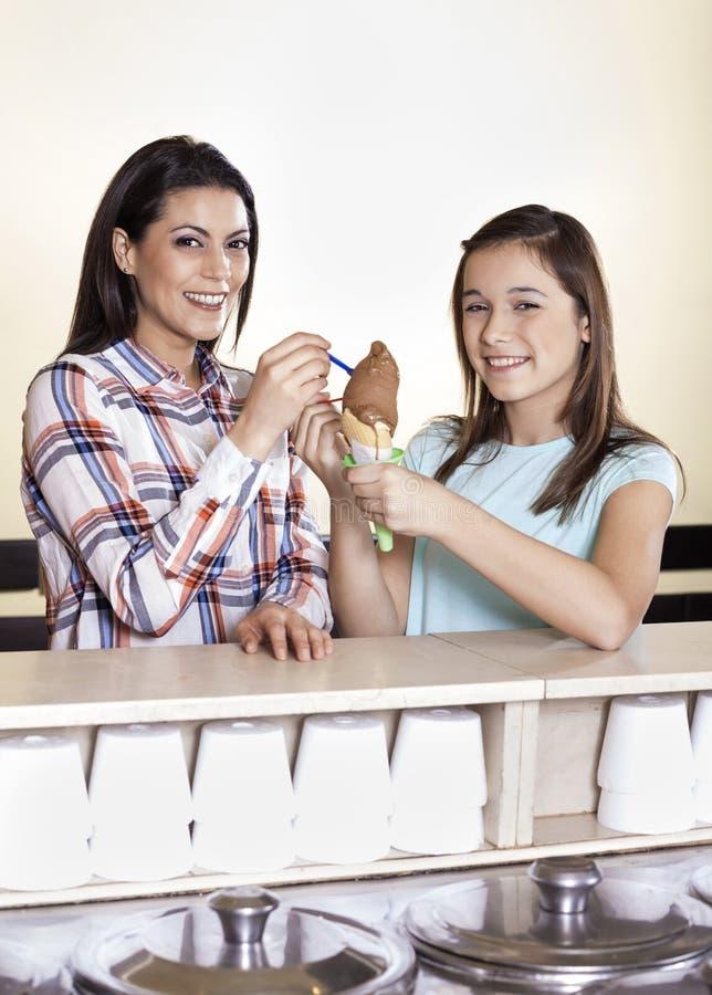 Mère heureuse et fille ayant la crème glacée de chocolat au compteur photographie stock libre de droits