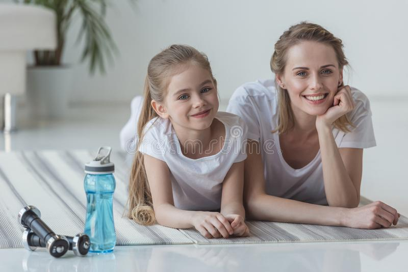 mère heureuse et fille d'ajustement se trouvant sur des tapis de yoga image stock