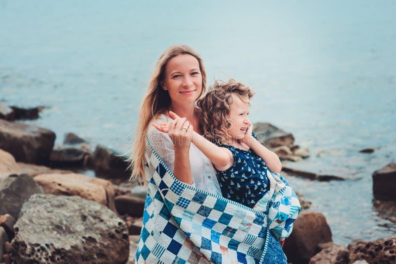Mère heureuse et fille enveloppées dans le temps passant couvrant d'édredon ensemble sur la plage des vacances d'été Déplacement  photo libre de droits