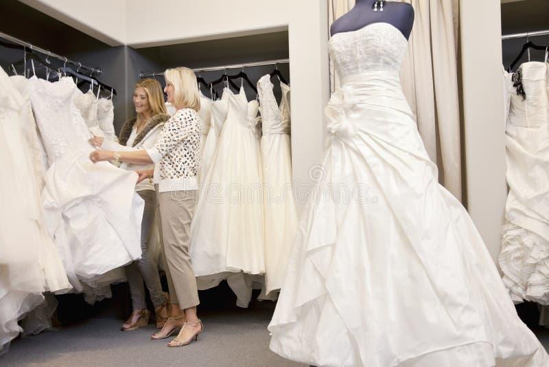 Mère heureuse et fille faisant des emplettes ensemble pour la robe de mariage dans la boutique photo libre de droits