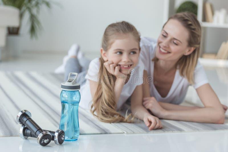 mère heureuse et fille folâtres se trouvant sur des tapis de yoga image stock