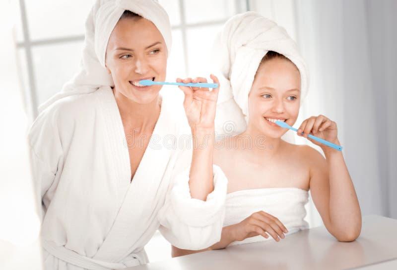 Mère heureuse et fille joyeuses se brossant les dents photo stock