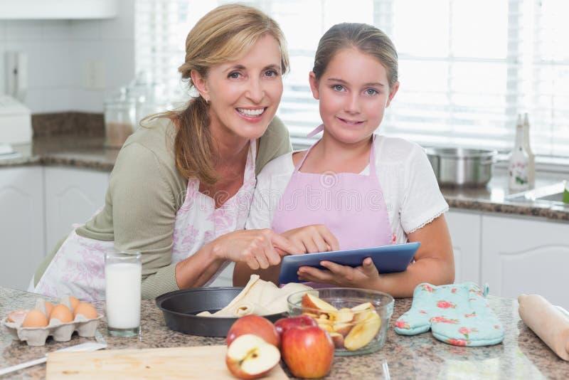 Mère heureuse et fille préparant le gâteau ensemble photos stock