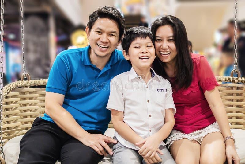 Mère heureuse et fils de père de famille de sourire s'asseyant sur le bambou public d'oscillation image libre de droits