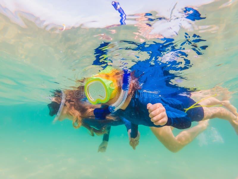 Mère heureuse et fils naviguant au schnorchel en mer Regardez les poissons sous l'eau photo libre de droits
