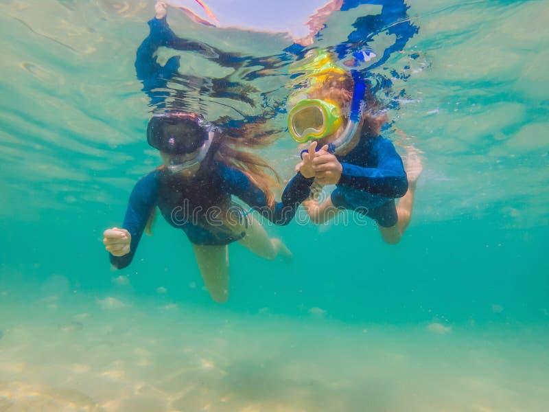 Mère heureuse et fils naviguant au schnorchel en mer Regardez les poissons sous l'eau image libre de droits