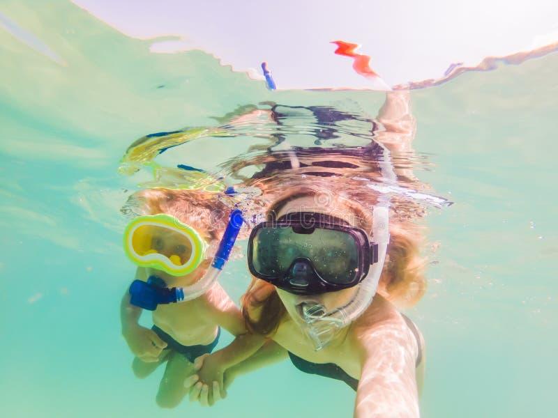 Mère heureuse et fils naviguant au schnorchel en mer Regardez les poissons sous l'eau photographie stock libre de droits