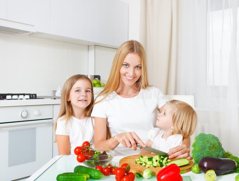 Mère heureuse et ses petites filles dans la cuisine images libres de droits