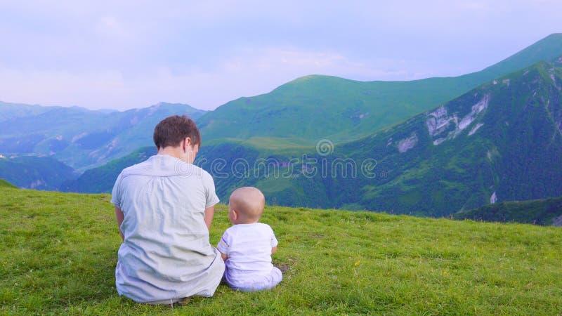 Mère heureuse et son enfant semblant en avant et indiquant le ciel Famille le jour de trekking dans les montagnes photographie stock libre de droits