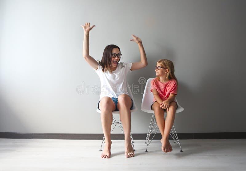 Mère heureuse et son petit dérivé s'asseyant sur les chaises par le Th photo stock