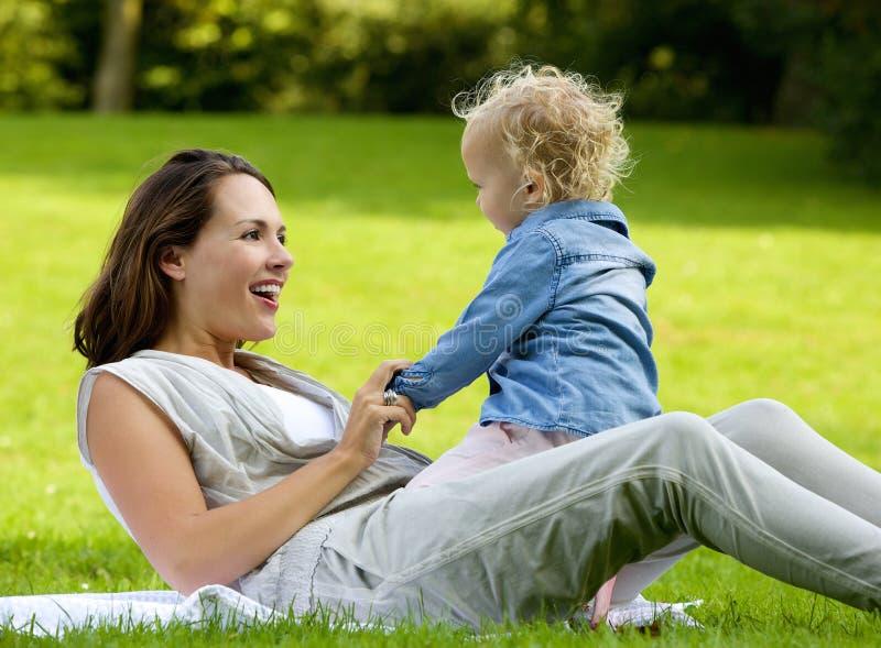 Mère heureuse jouant avec la fille de bébé dehors photo libre de droits