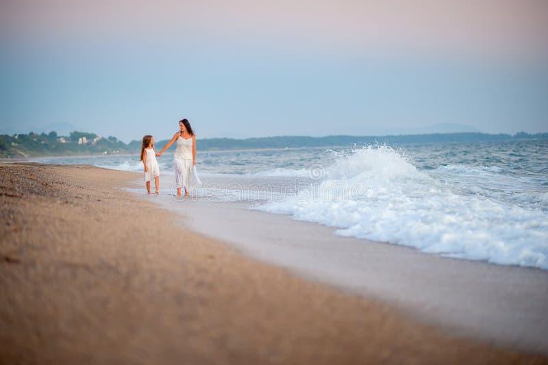 Mère heureuse marchant avec sa fille aimée sur la plage au coucher du soleil photos libres de droits