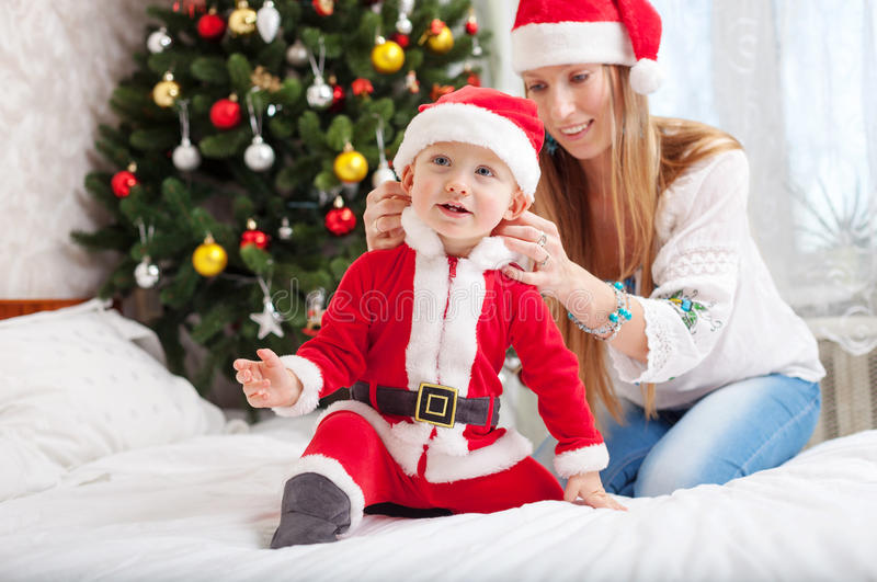 Mère heureuse mettant le costume de Santa sur le fils d'enfant en bas âge image stock
