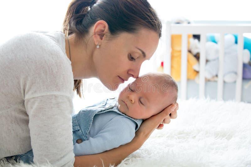 Mère heureuse, parlant à son fils nouveau-né, frottant et embrassant h photographie stock libre de droits