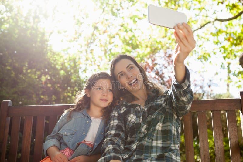 Mère heureuse prenant le selfie avec la fille tout en se reposant sur le banc en bois photos libres de droits