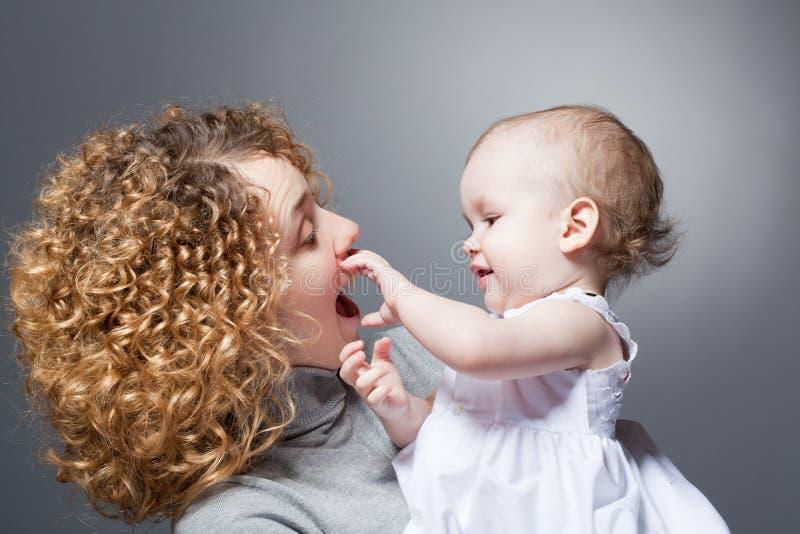 Mère heureuse retenant la chéri de sourire mignonne image stock