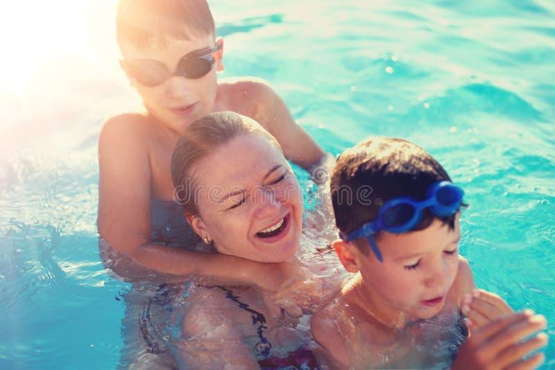 Mère heureuse riant avec des fils dans la piscine images libres de droits