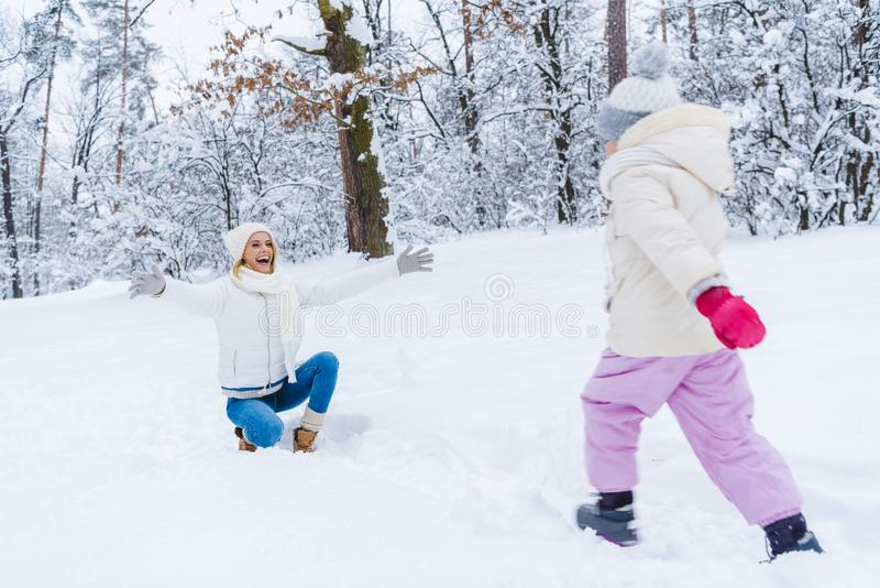 mère heureuse se mettant à genoux avec les bras ouverts et petite la fille marchant dans la neige images stock