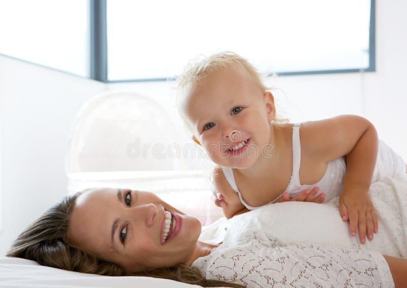 Mère heureuse souriant avec la petite fille mignonne photographie stock