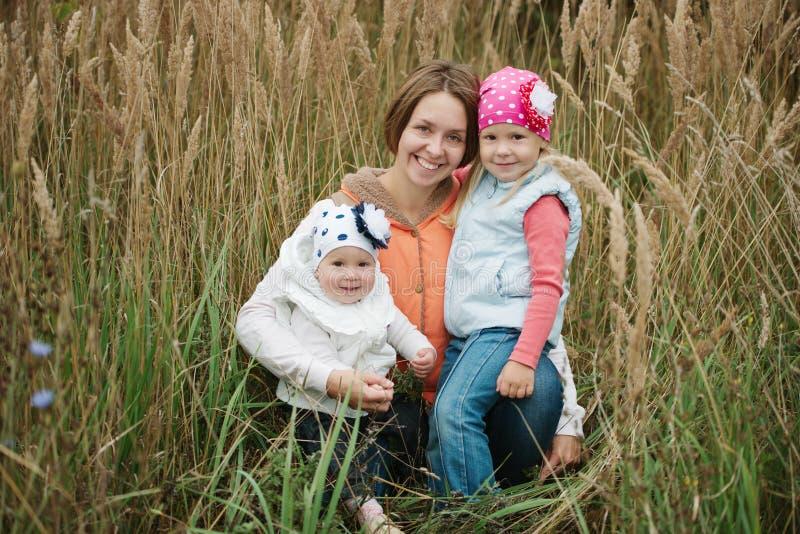 Mère heureuse tenant deux petits daughers image libre de droits