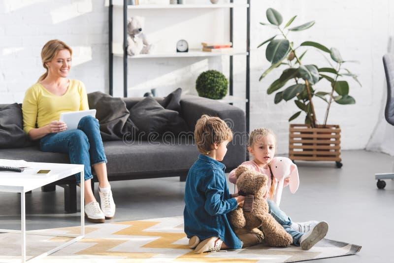 mère heureuse utilisant le comprimé numérique et regarder le jeu adorable d'enfants photographie stock libre de droits