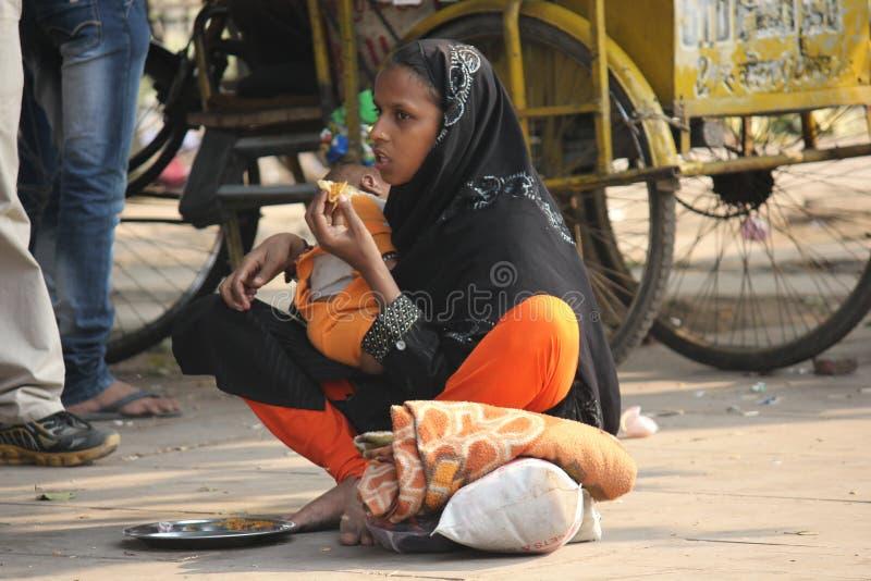 Mère indienne demandant la charité avec son bébé image stock