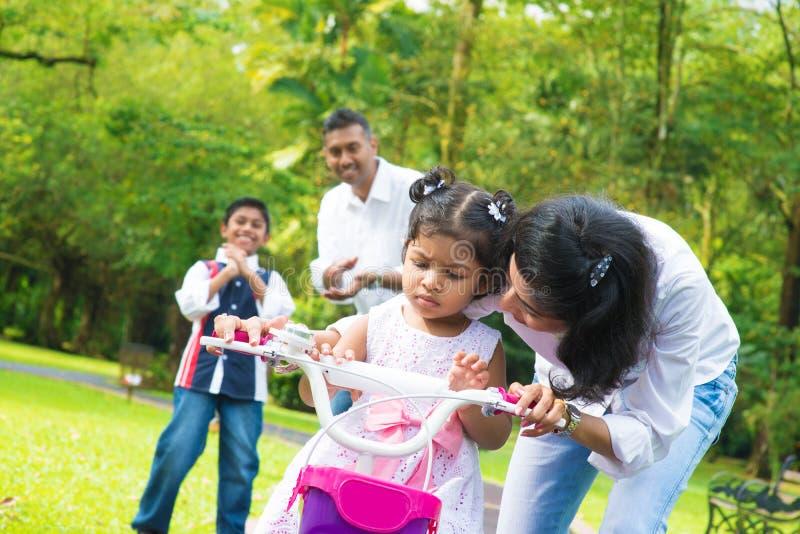 Mère indienne enseignant la petite fille à monter un vélo image stock